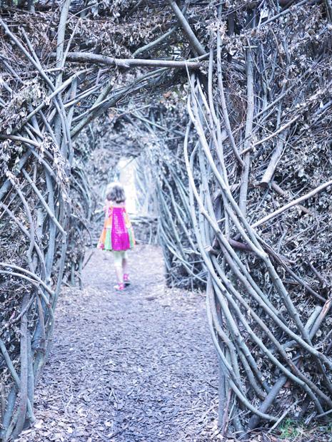 Une petite fille tout en rose s'aventure dans le labyrinthe - Exposition 56 chandelles